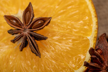 Half An Orange And A Star Anise On A Wooden Table.