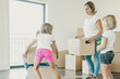 canvas print picture - Happy family with two kids holding cardboard boxes and running into new home. Cute little girls helping parents with belongings in big apartment or house. Mortgage, relocation and moving day concept