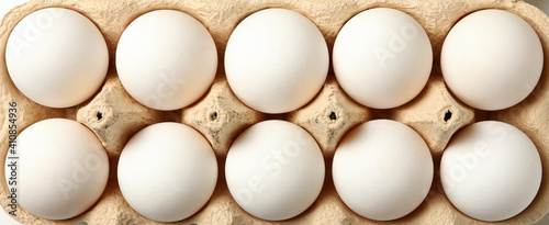 Fotografia Egg box with fresh eggs on whole background, top view
