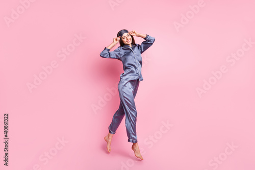 Obraz Full length body size photo of brunette in blue pajama jumping smiling touching sleeping mask isolated on pastel pink color background - fototapety do salonu