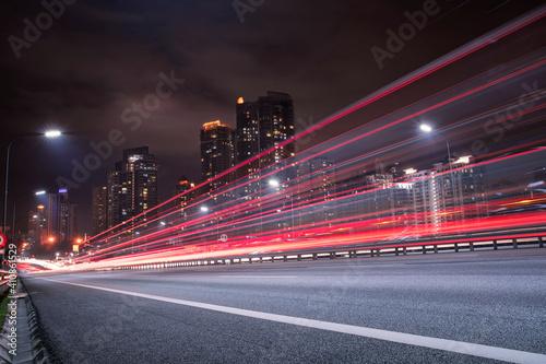 Fotografia Light Trails On City Street Against Sky At Night