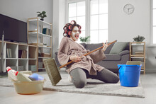 Cheerful Young Woman Having Fun And Revealing Hidden Talent While Cleaning House. Crazy Housewife In Hair Curlers And Face Mask Tidying Up Home, Singing Funny Songs And Playing On Pretend Mop Guitar