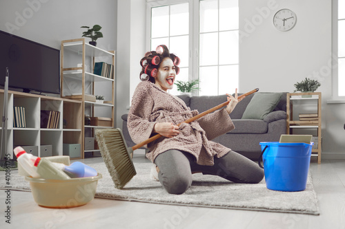 Fotografia Cheerful young woman having fun and revealing hidden talent while cleaning house