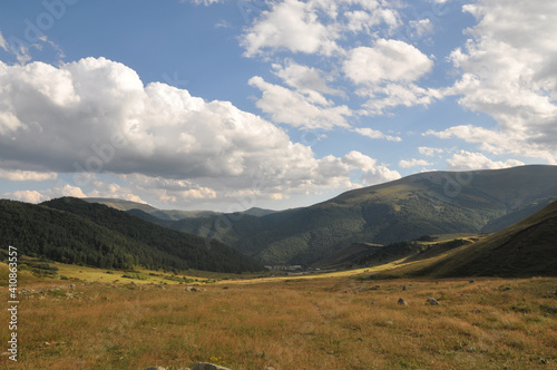 Landscape of green meadow with trees on the hillside under a cloudy sky in Armen Fototapet