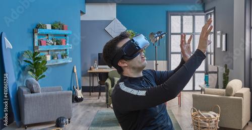 Obraz Close up man with virtual reality goggles, decorative blue wall background. - fototapety do salonu