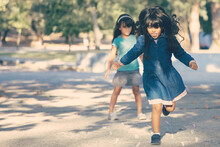 Two Excited Black Haired Little Girls Playing Hopscotch In City Park. Full Length, Copy Space. Childhood Concept