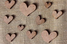 Decorative Wooden Hearts On Burlap Canvas Background, Love And Valentine's Day Concept