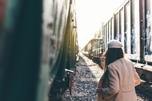 Portrait Of A Girl In A Beret And Beige Jacket Between Two Vintage Train Cars.