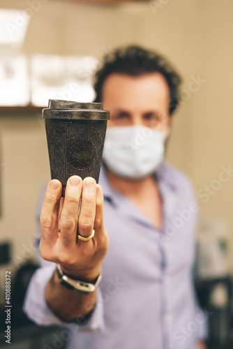 Handsome barista with a face mask making a cup of coffee at the coffee shop- Covid-19 © Wirestock
