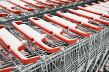 Row Of Stacked Metal Shopping Trolley Carts With Red Handles Near Of Supermarket Covered With Snow. Financial Crisis, Economy Depression, Frozen Market Problems Concept.