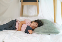 Asian Cute Little Girl Watching Cartoon In Smartphone While Lying In A Blanket Fort In Living Room At Home For Perfect Hideout Away From Their Other Family Members And For Them To Play Imaginatively.