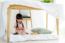 Asian Cute Little Girl Play Her Doll While Sitting In A Blanket Fort In Living Room At Home For Perfect Hideout Away From Their Other Family Members And For Them To Play Imaginatively.