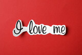 Piece of paper with handwritten phrase I Love Me on red background, top view
