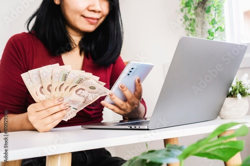 Asian woman holding Thai money using smart phone and laptop on desk, register, p Fototapeta