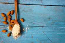 Almond Flour In A Bowl And Spoon With Scattered Nuts On An Old Wooden Table