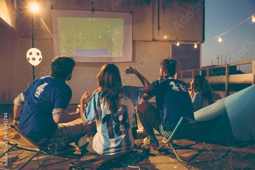Obraz na plátně Friends watching football on a building rooftop terrace