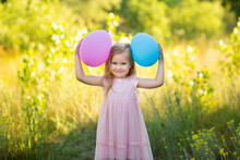 A Girl In A Pink Dress Stands In A Field On The Grass On A Summer Day And Holds Balloons In Her Hands