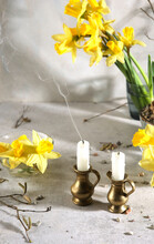 Two Candles With Daffodil Flowers Indoor. Extinguished Candles In Jug Candlesticks.