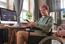Disabled Woman With Short Hair Sitting On Wheelchair And Working Online On Mobile Phone During Her Work On Computer At Home