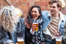People Enjoying A Beer Together At Pub Brewery - Happy Laughing Man And Women Talking And Raising Pint Glass - Lifestyle And Drink Concepts In London