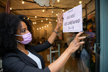 Portrait Of A Beautiful Young Owner Of A Clothing Store While Hanging A Sign In The Window For The Reopening Of The Business Wearing The Protective Face Mask Against Coronavirus Infections, Covid-19
