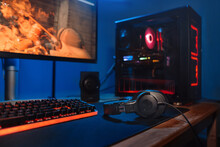 Computer Gamer Workplace With New Game Keyboard, Mouse, Headphones, Modern Pc With Blur Blue And Red Neon Light. Powerful Personal Computer For E Cyber Sport Gamer On The Table At Home. Close Up