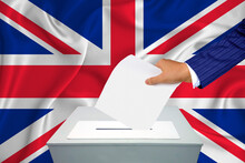 Elections In The Country - Voting At The Ballot Box. A Man's Hand Puts His Vote Into The Ballot Box. Flag Great Britain On Background.
