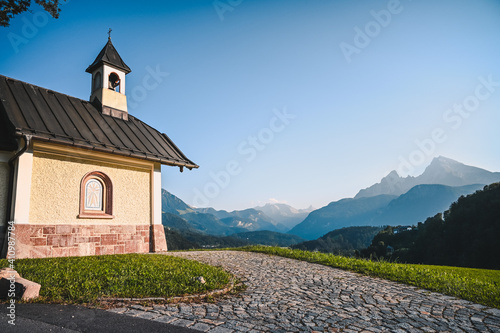 Fotografiet Amazing alpine panorama with the Kirchleitn chapel in the front and the the huge Watzmann mountain in the background under a clear blue sky