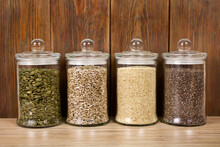 Pumpkin, Sunflower, White Sesame And Chia Seeds In The Trendy Glass Jars On A Wooden Background. Superfood And Healthy Eating Concept.