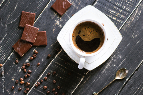 Canvas Top view of a cup of coffee on a table with chocolate