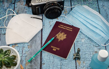 Concept Of Covid Vaccine Tourism.  Top View Of A Passport And A Syringe On A Blue Table.