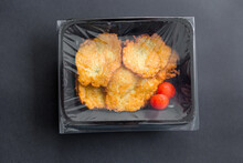 Potato Pancakes In Transparent Sealed Packaging On Black Background, Top View. Food Delivery In Take Away Box