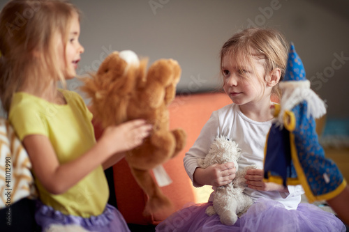Obraz A little sisters playing with dolls at home. Children, home, playing - fototapety do salonu