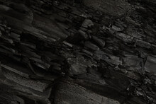 Black, Dark Aged Shabby Cliff Face, Divided By Huge Cracks, Tectonics Layers. Coarse, Rough Gray Stone, Rock Texture Of Mountains, Background, Copy Space For Text On Theme Geology, Mountaineering.