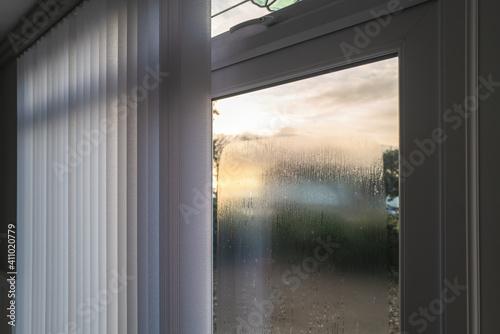 Obraz Condensation on the outside of double glazed window glass at sunrise. The window has vertical slat blinds. - fototapety do salonu