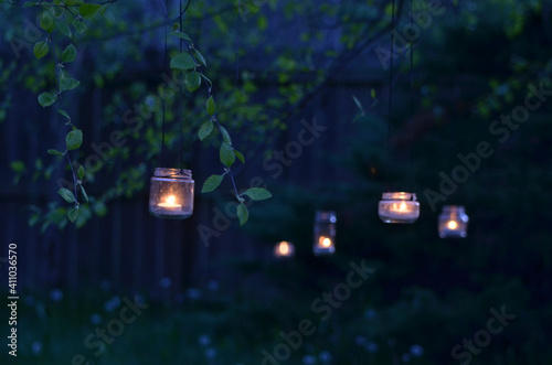 Fototapeta Upcycled Glass Jar Garden Lanterns Illuminated By Candles Hang From Tree Branche