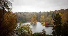 Amazing Nature Scene Of A Small Lake Surrounded By Colorful Dense Autumn Folia