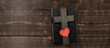 Bible book on a wooden table. Wooden cross of Jesus. Red heart. The concept of love for God's Word.