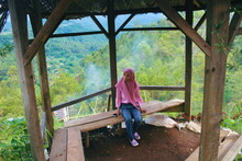 High Angle View Of Teenage Girl Sitting On Bench In Gazebo At Mountain