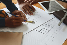 Cropped Hands Of Architects Drawing Blueprint At Desk