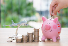 Close-up Of Hand Inserting Coins In Piggy Bank By Model Airplane