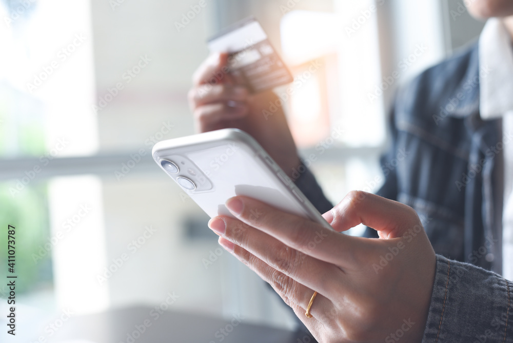 Fototapeta Mobile banking, Online shopping, digital banking, internet payment concept. Woman hand using mobile smart phone payments and credit card for online shopping