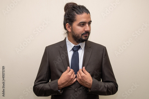Tela Man in a suit and a blue tie with his hands on his chest adjusting the suit and