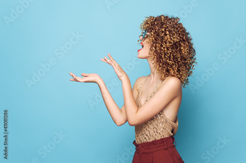 Canvas Print Attractive woman curly hair Gesturing hands side view blue background