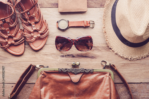 Fototapeta High Angle View Of Leather Purse With Sandals And Hat On Table obraz