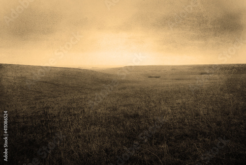 Fototapeta Stylized Foggy Grassland Background with Rolling Hills, Gritty Sepia Texture, an