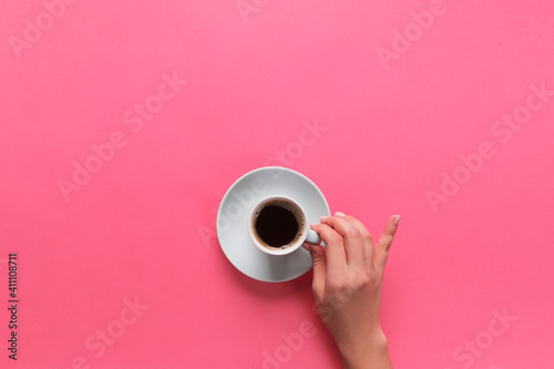 Directly Above View Of Hand Holding Coffee Cup Against Pink Background