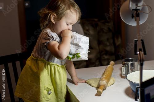 Fotografija infante girl cooks food in the kitchen