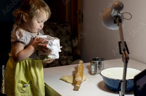 infante girl cooks food in the kitchen Fototapeta