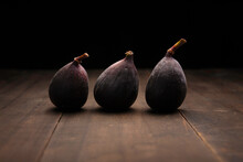 Image Of Three Common Figs Fruits Close Up On Rustic Wooden Surface And Black Background